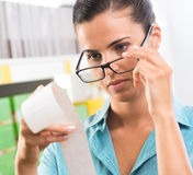 Woman with glasses checking a receipt Stock Photo