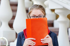 Woman in glasses covering her face with red folder Royalty Free Stock Photo