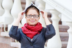 Woman in glasses covering her head with book Stock Photos