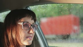 A woman in glasses driving a car. stock video