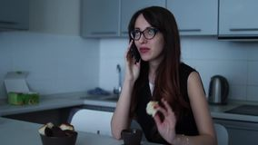 Woman in glasses eating food and talking on the mobile phone at kitchen. Woman eating cookies and drinking coffee in the kitchen. Full HD Resolution 1920x1080 stock video