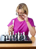 Woman in glasses examines chess king isolated Stock Images