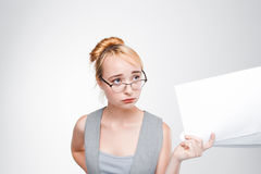 Woman in glasses feels disappointed and grieved. Young woman in glasses with papers in hand feels disappointed, grieved, sad and chagrined. Failure, bad luck Royalty Free Stock Photo