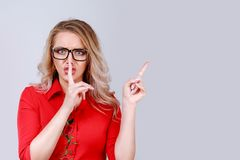 Woman in glasses gesturing silence and pointing stock images