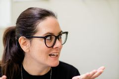 A Woman in Glasses Gesturing to Someone on the Left stock images