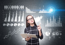 Woman in glasses and graphs on blackboard Royalty Free Stock Photo