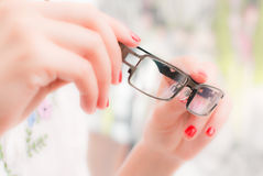 Woman with glasses in hands. Woman holding her glasses through her hands Royalty Free Stock Image