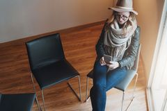 Woman in glasses and hat is sitting in room, using smartphone. Girl checks e-mail, looks for information about sights. Young woman in glasses and hat is sitting Stock Images