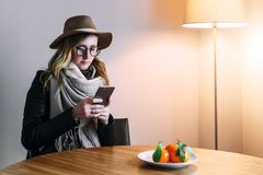 Woman in glasses and hat is sitting in room, using smartphone. Girl checks e-mail, looks for information about sights. Young woman in glasses and hat is sitting Royalty Free Stock Images
