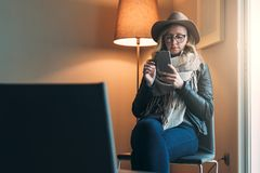 Woman in glasses and hat is sitting in room, using smartphone. Girl checks e-mail, looks for information about sights. Young woman in glasses and hat is sitting Royalty Free Stock Photography