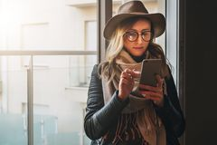 Woman in glasses and hat is standing in room near window, using smartphone. Hipster girl checks email, browsing internet. Young woman in glasses and hat is Stock Photo