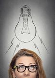 Woman with glasses having an idea looking up. Headshot thinking businesswoman with glasses having an idea looking up with light bulb over her head isolated grey Stock Photo