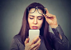 Woman with glasses having trouble seeing cell phone has vision problems. Closeup woman with glasses having trouble seeing cell phone has vision problems Stock Images