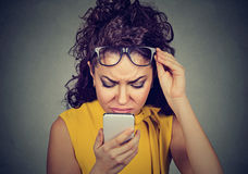 Woman with glasses having trouble seeing cell phone vision problems. Closeup young woman with glasses having trouble seeing cell phone has vision problems. Bad Stock Photo