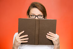 Woman with glasses hiding face behind book. Shy, secret. Closeup portrait woman with glasses hiding face behind book looking at camera suspicious isolated red Stock Images