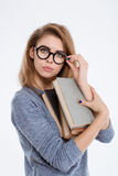 Woman in glasses holding books and looking at camera. Portrait of a young woman in glasses holding books and looking at camera isolated on a white background Stock Photos