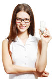 Woman in glasses holding lamp. Beautiful young woman in glasses holding energy saving lamp bulb Royalty Free Stock Photos