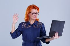 A woman with glasses is holding a laptop and waving her hand to print on a gray background. A woman, aged with red hair, in a blue dress, with glasses, holds a Stock Photos