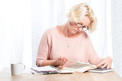 Woman in Glasses Holding Pen Turns Book Page Royalty Free Stock Photo