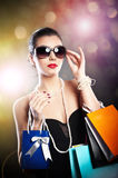 Woman with glasses holding shopping bags against a black background Stock Images