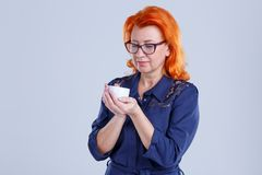 A woman with glasses holds a mug in her hands and looks at it against a gray background. A woman, aged with red hair, in a blue dress, with glasses, holds a mug Stock Image