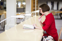 Woman with glasses in library study text. Young woman with glasses in library study text Royalty Free Stock Image