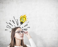 Woman in glasses, light bulb, exclamation marks Stock Photos