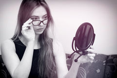 Woman with glasses looking in the mirror. Black and white with delicate pink colour Royalty Free Stock Image