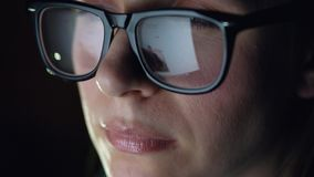 Woman in glasses looking on the monitor and surfing Internet. The monitor screen is reflected in the glasses stock video footage
