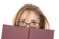 Woman glasses looking over book. A woman in glasses peeking over the top of her book Royalty Free Stock Images