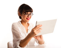 Woman with glasses, looking at tablet computer. Professional young woman with glasses and red lipstick, sitting at a desk with a tablet computer Royalty Free Stock Images