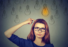 Woman in glasses looking up with light idea bulb above head. Thinking woman in glasses looking up with light idea bulb above head isolated on gray wall Royalty Free Stock Photo