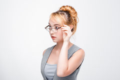 Woman in glasses looks distrustful and doubtful. Young woman in glasses looks distrustful, doubtful, timid and apprehensive. Grey background with copy space Royalty Free Stock Photo