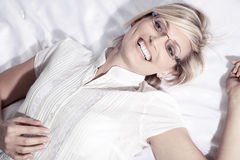 Woman with glasses lying on back and laughs Royalty Free Stock Photography
