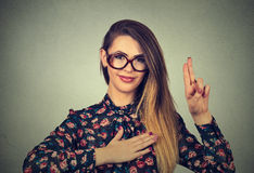 Woman in glasses making a promise isolated on gray wall background Stock Image