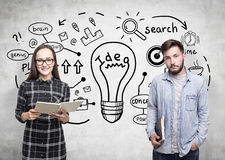 Woman in glasses and a man, business idea. Portrait of a men and a women in glasses standing near a concrete wall with a business idea sketch on it Royalty Free Stock Images