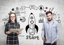 Woman in glasses and a man, start up. Portrait of a men and a women in glasses standing near a concrete wall with a start up sketch on it Royalty Free Stock Photo