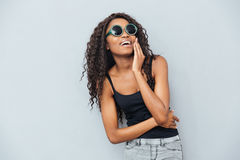 Woman in glasses posing over gray background. Cheerful afro american woman in glasses posing over gray background Royalty Free Stock Photo