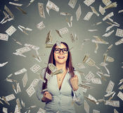 Woman in glasses pumping fists celebrates success under money rain Royalty Free Stock Photos