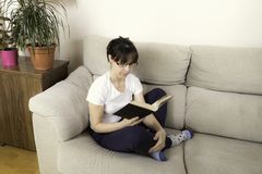 Woman with glasses reading a book on a sofa Royalty Free Stock Photo