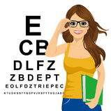 Woman with glasses reading sight test characters Stock Photos
