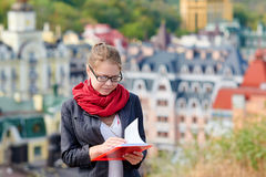 Woman in glasses with the red book on city background Royalty Free Stock Photos