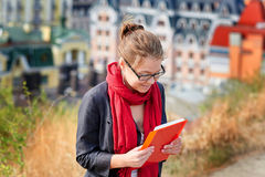 Woman in glasses with the red book on city background Stock Photo