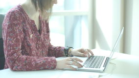 Woman in glasses with short hair kare and rings on his fingers, looking at laptop screen and pushes buttons on keypad. She sits at a table in spacious and stock video footage