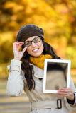 Woman with glasses showing digital tablet in autumn Stock Images