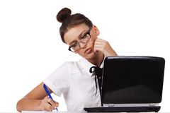 Woman with glasses sits at a table and working Royalty Free Stock Images