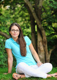 Woman in glasses sitting in a park Royalty Free Stock Photos