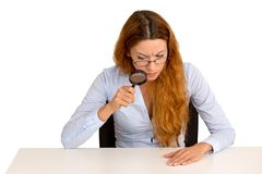 Woman with glasses skeptically looking through magnifying glass Stock Image
