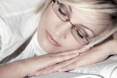 Woman with glasses sleeps on book Stock Photography