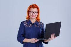 A woman with glasses with a small smile is holding a laptop on a gray background. A woman, aged with red hair, in a blue dress, with glasses with a slight smile Royalty Free Stock Photo